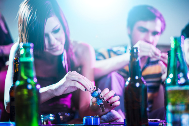 alcohol and cannabis people packing a bowl drinking